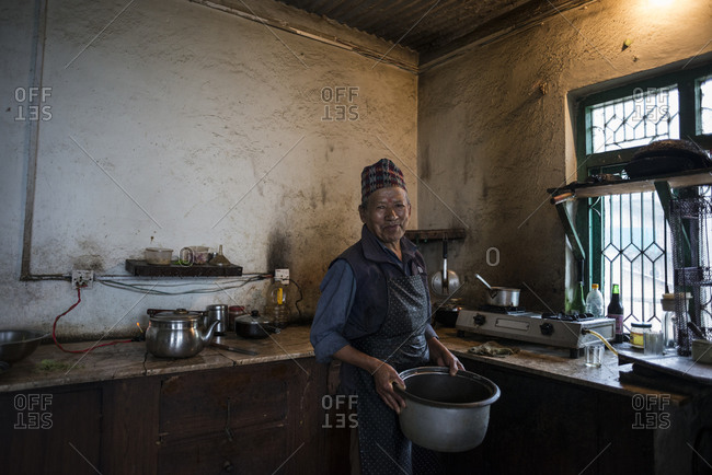 Dolakha, Nepal - June 7, 2014: A man cooks in his kitchen in Dolakha, Nepal