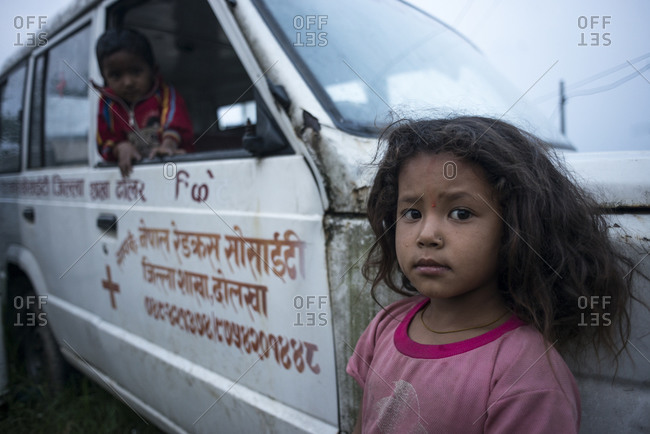 Dolakha, Nepal - June 6, 2014: A little girl leans against the side of a van