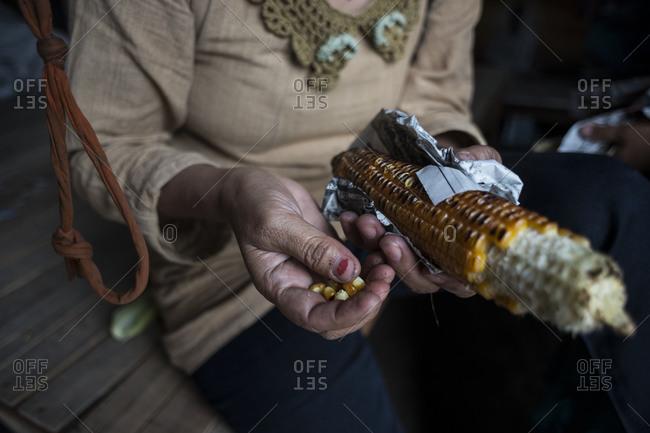 A woman picks kernels off the cob, Nepal