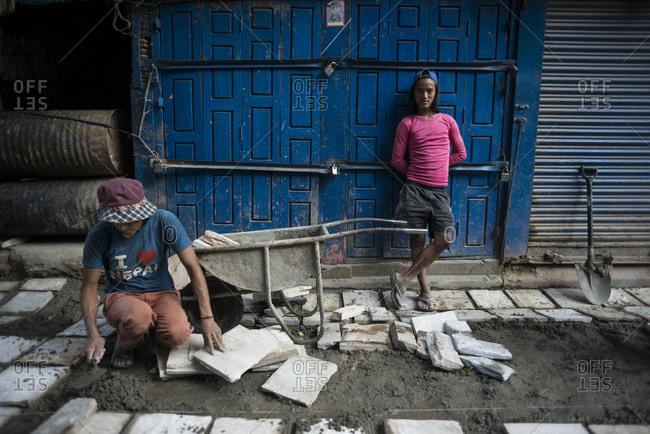 Kathmandu, Nepal - June 2, 2014: Two men repair a road in a city in Nepal