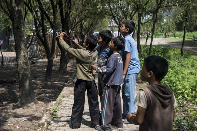 Kathmandu, Nepal - May 29, 2014: Little boys shoot a slingshot in the slums of Thapathali, Kathmandu, Nepal