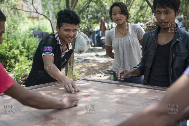 Kathmandu, Nepal - May 29, 2014: Young men play a tabletop game in the slums of Thapathali, Kathmandu, Nepal