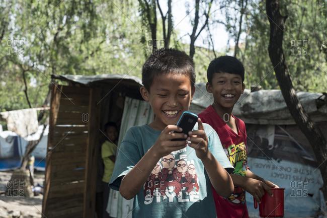 Kathmandu, Nepal - May 29, 2014: Young boys laugh while looking at a phone in the slums of Thapathali, Kathmandu, Nepal