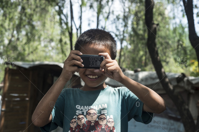 Kathmandu, Nepal - May 29, 2014: A boy takes a photograph with a cell phone in the slums of Thapathali, Kathmandu, Nepal