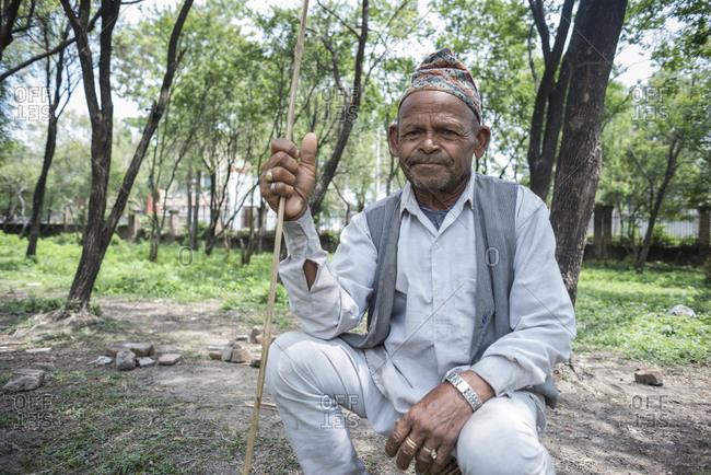 Kathmandu, Nepal - May 29, 2014: An old man holding a stick in the slums of Thapathali, Kathmandu, Nepal