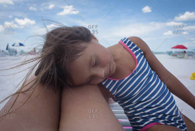 Young girl affectionately leans her head on her mother's legs at the beach