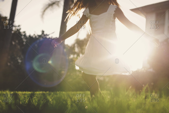 Young girl in white dress spinning in the sunlight on grassy lawn