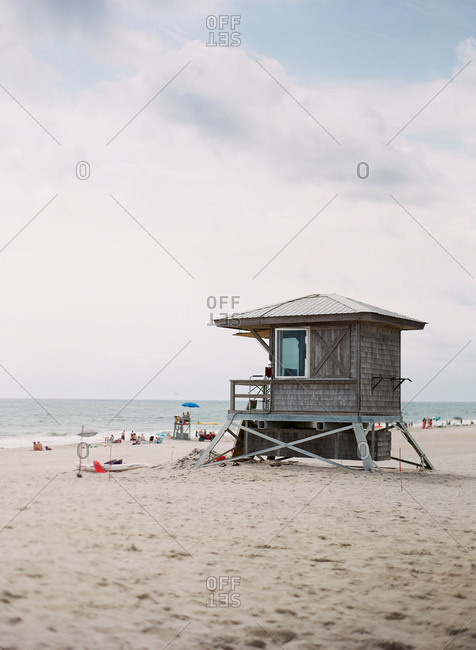 Wood shingled lifeguard station on beach with beachgoers in background