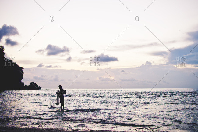 Fisherman with net at the shore