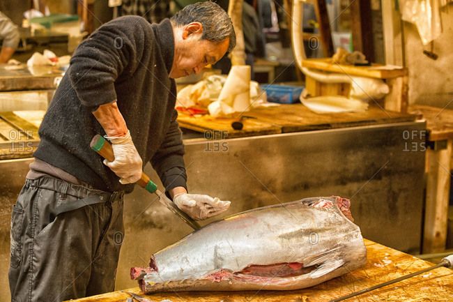 Tokyo, Japan - April 12, 2012: A man slices a massive fish at the Tsukiji Fish Market