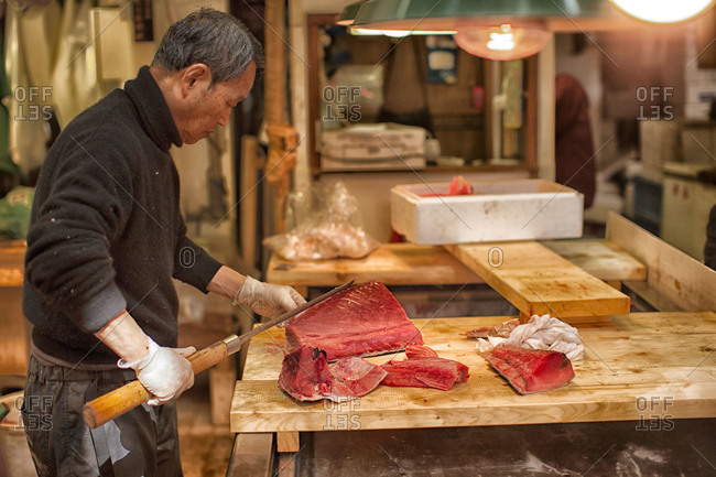 Tokyo, Japan - April 12, 2012: A man slices a fish with a  massive knife at the Tsukiji Fish Market