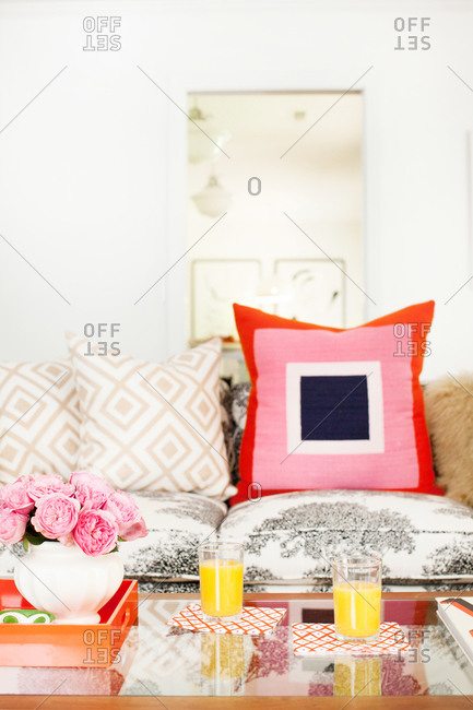 A large pink and blue throw pillow on a couch