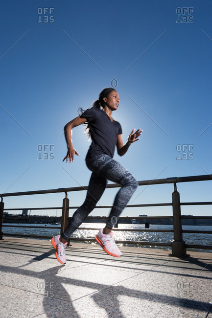 Athletic woman sprinting at oceanside park