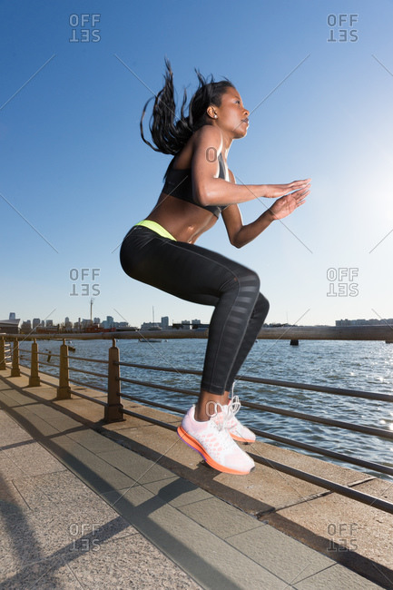 Athletic woman doing jump tucks at oceanside park