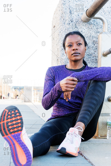 Athletic woman sitting against railing resting