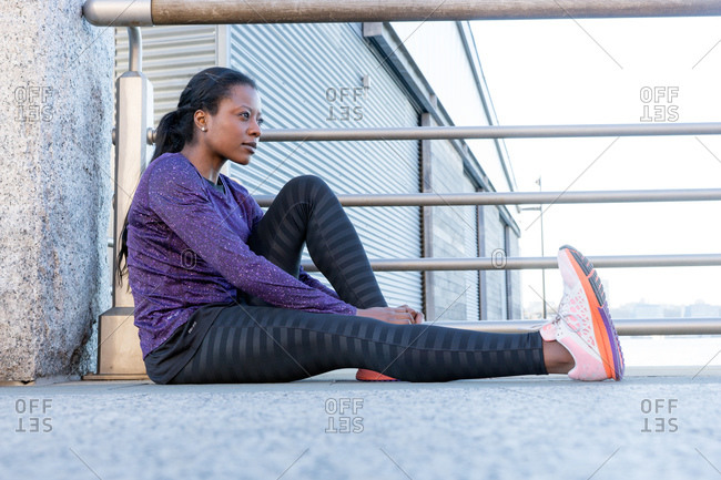 Athletic woman sitting resting by railing