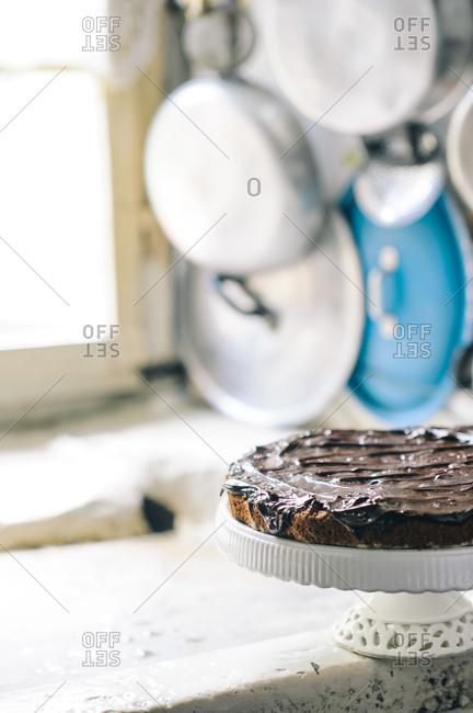 A flat chocolate cake the edge of a windowsill