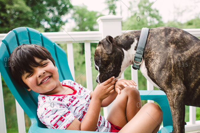 Boy being licked by dog sitting on deck