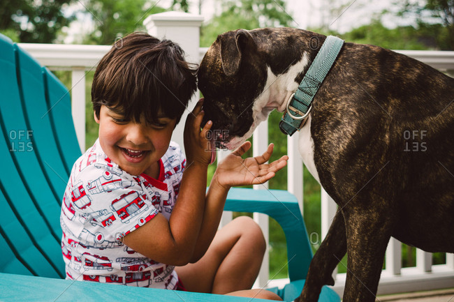 Boy being licked by dog sitting on porch
