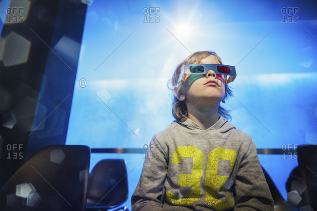 A young boy sits in theater wearing 3D glasses