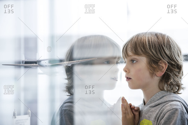 A little boy looks at a model airplane in a display case