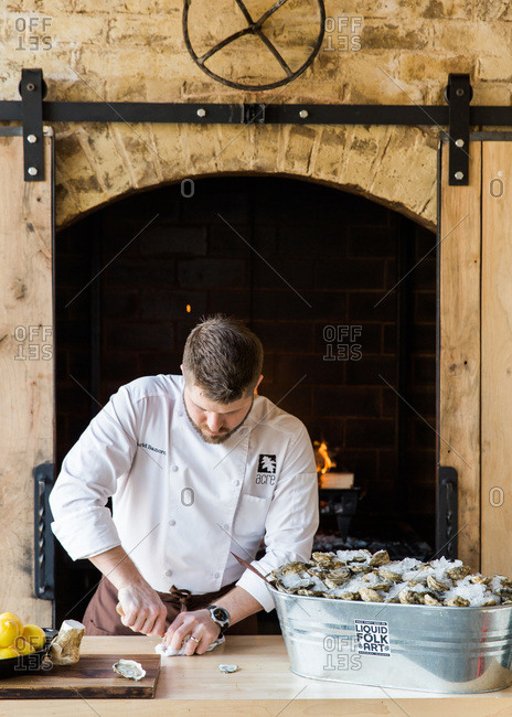Auburn, Alabama - January 24, 2014: Head chef and owner David Bancroft of Acre shucks oysters near his smoking oven at Acre