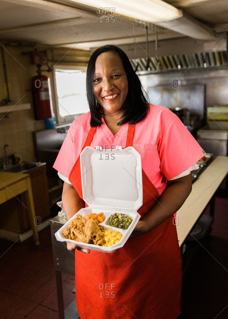 Hattiesburg, Mississippi - November 8, 2013: Brenda Williams, owner and cook at Home Style Restaurant  shows off one of her famous fried chicken lunches