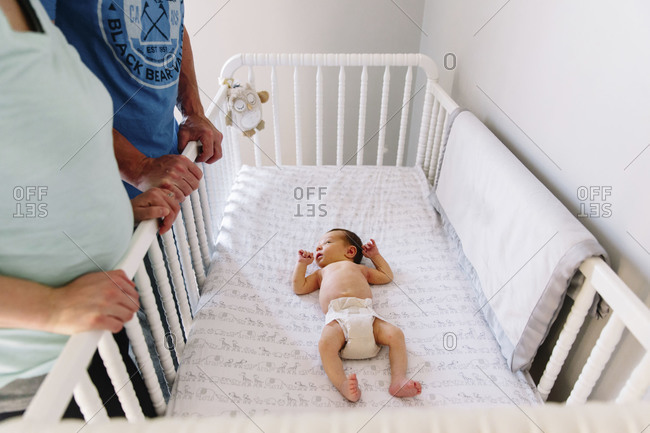 Parents looking down on newborn in crib