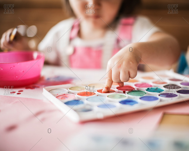 A toddler uses watercolor paints to fingerprint