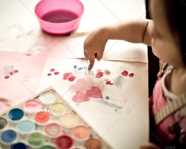 A little girl uses watercolor paint to fingerprint