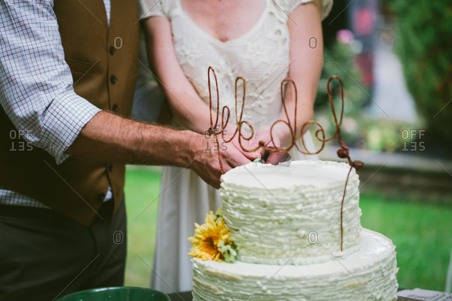 A bride and groom cut their wedding cake
