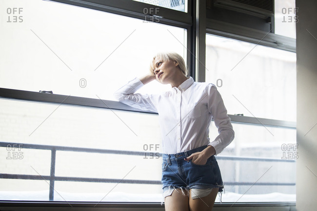 A young woman in a white button-down shirt looks out the window