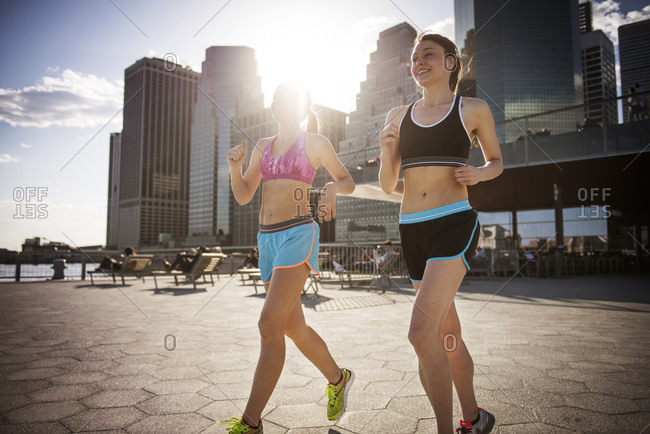 Two women jog by the edge of a river in the city