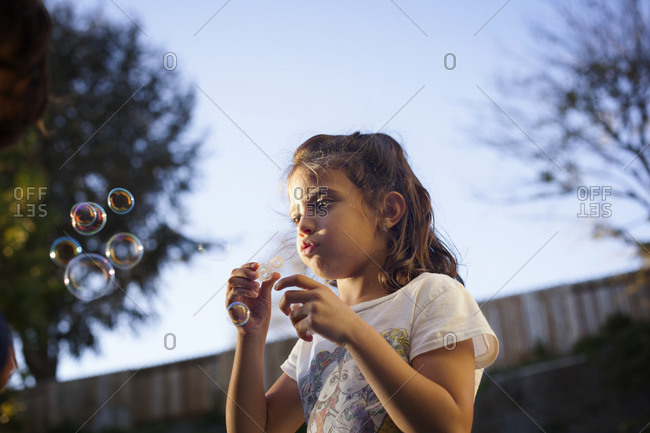 Upward view of young girl blowing bubbles in backyard