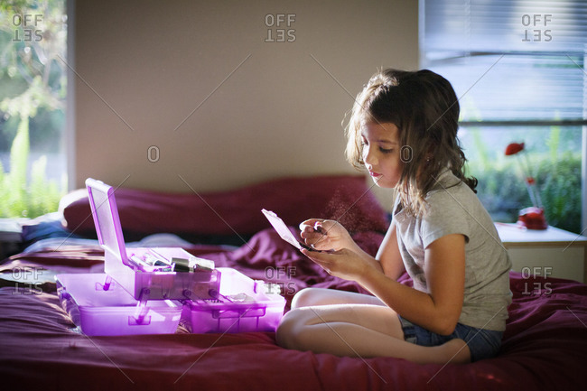 Young girl putting on makeup while sitting on bed