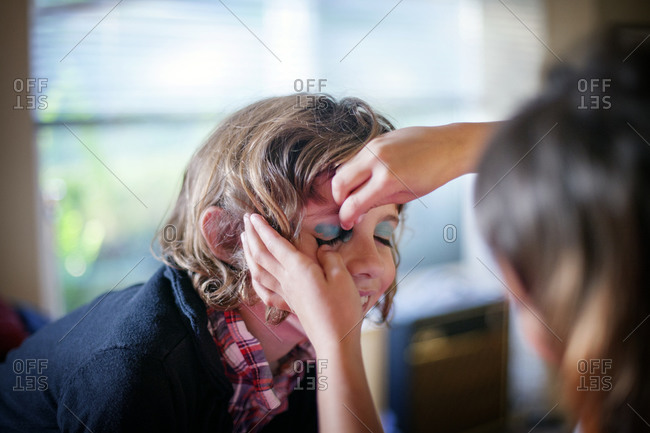 Young girl holding still while green eye shadow is being applied to her by another child