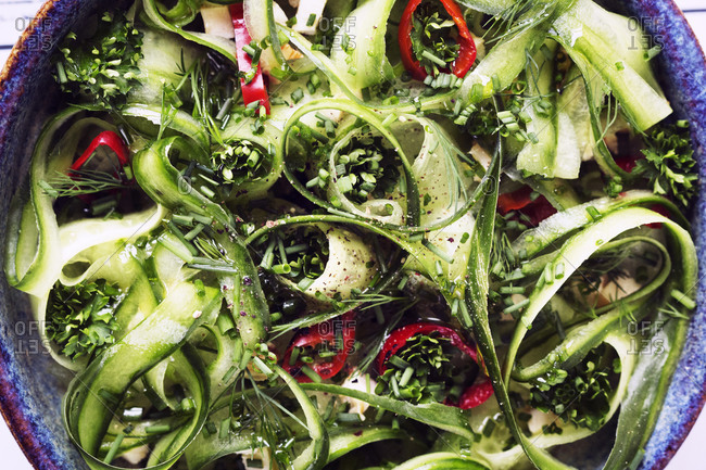 Close up of a salad with cucumber, red pepper, parsley and chives