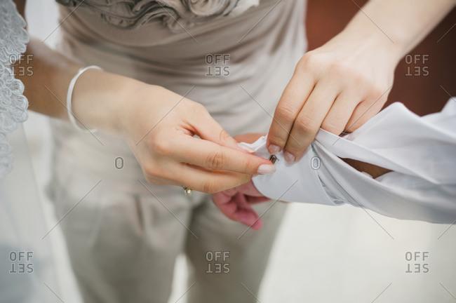 Woman helping man with cufflinks