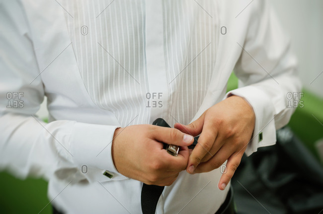 Man getting ready for wedding and putting on suspenders