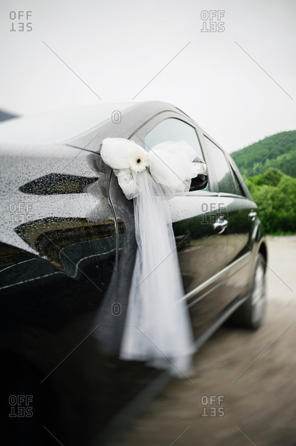 Luxury car decorated with wedding flowers and ribbon