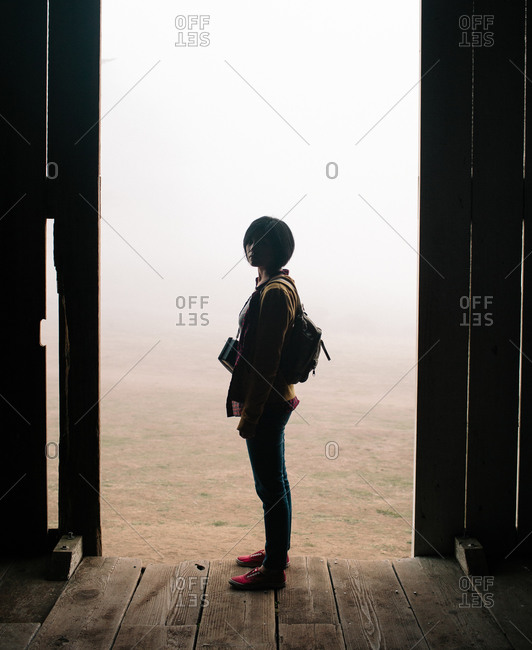 Woman standing at the entrance of a barn in Point Reyes, California