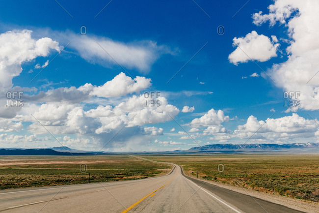 An empty road turns through a plain towards mountains
