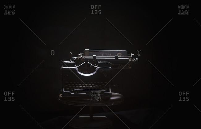 Typewriter on table against black background