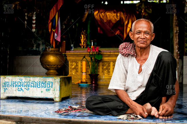 Battambang, Cambodia - September 19, 2012: A Cambodian man smiling in front of a temple