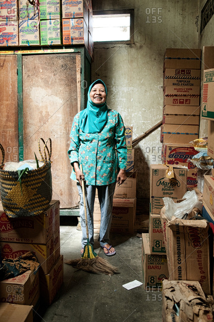Yogyakarta, Indonesia - May 29, 2015: An Indonesian woman with a broom in her grocery store