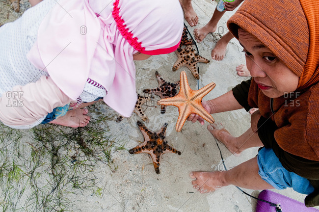 Lombok, Indonesia - May 29, 2015: Two muslim women looking for starfish on the beach