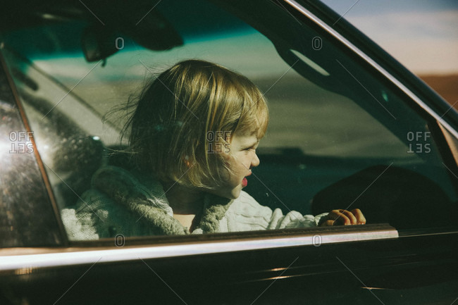 Child staring out window of car