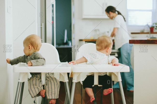 Toddlers in high chair as mom prepares food