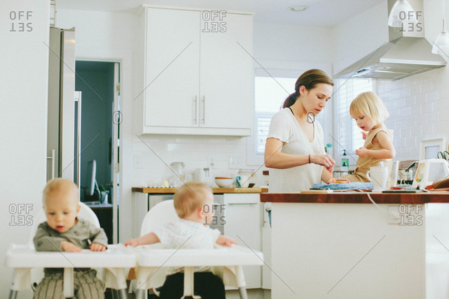 Mom with three young children in kitchen