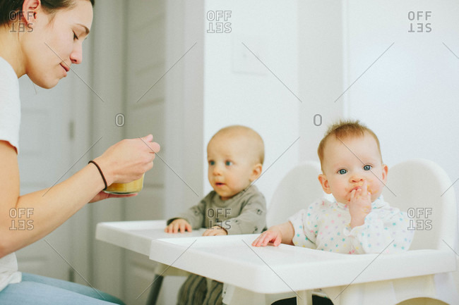 Mom feeding toddlers in high chairs